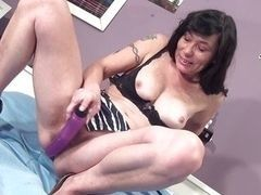 Dark-haired mature lady satisfying herself dildo