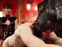 Redhead mistress in latex drills strap-on of the slave in mask and with gag
