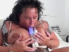 Plump mature brunette with the huge breast playing with her sex toy