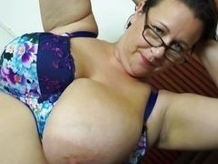 Mature lady wearing spectacles plays with the huge tits