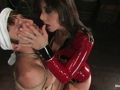 Mistress in red latex dominating over the man and tormenting him cock